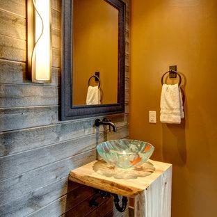 Стильный дизайн: туалет в стиле рустика с настольной раковиной, столешницей из дерева, коричневыми стенами и бежевой столешницей - последний тренд