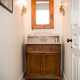 На фото: маленький туалет в стиле кантри с белыми стенами, фасадами островного типа, полом из керамической плитки, врезной раковиной, столешницей из известняка и темными деревянными фасадами с