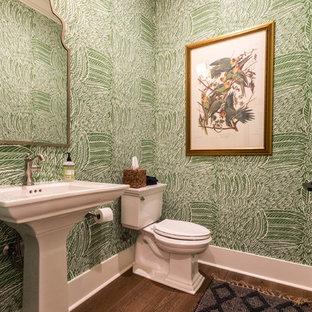 На фото: туалет в стиле современная классика с зелеными стенами, раковиной с пьедесталом, темным паркетным полом и коричневым полом с