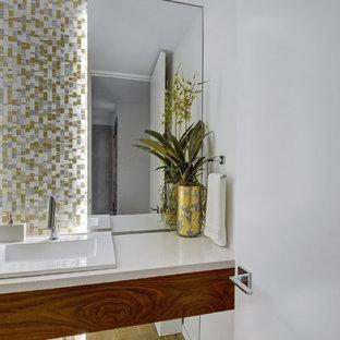 На фото: маленький туалет в современном стиле с плоскими фасадами, фасадами цвета дерева среднего тона, унитазом-моноблоком, белой плиткой, плиткой из листового стекла, белыми стенами, светлым паркетным полом, накладной раковиной, столешницей из кварцита и бежевым полом с