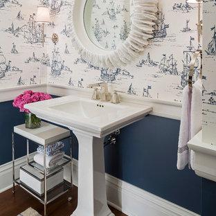 Idéer för mellanstora vintage toaletter, med blå väggar, ett piedestal handfat, en toalettstol med separat cisternkåpa, mellanmörkt trägolv och brunt golv