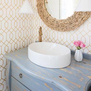 ミネアポリスの小さいビーチスタイルのおしゃれなトイレ・洗面所 (家具調キャビネット、ヴィンテージ仕上げキャビネット、マルチカラーの壁、ベッセル式洗面器、木製洗面台、分離型トイレ、淡色無垢フローリング、茶色い床、青い洗面カウンター) の写真
