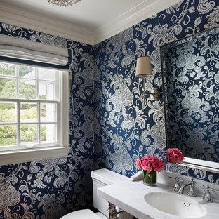 Ispirazione per un bagno di servizio tradizionale con lavabo a consolle, WC a due pezzi, pareti blu, top in marmo, pavimento marrone e parquet scuro