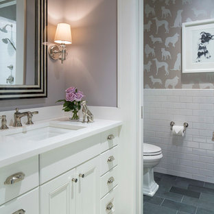 Photo of a medium sized traditional cloakroom in Minneapolis with white cabinets, slate flooring, grey floors, recessed-panel cabinets, a two-piece toilet, white tiles, metro tiles, purple walls, a submerged sink and quartz worktops.