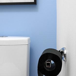 Идея дизайна: маленький туалет в стиле модернизм с плоскими фасадами, черными фасадами, синими стенами, паркетным полом среднего тона, монолитной раковиной, столешницей из кварцита и коричневым полом