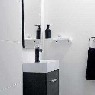 トロントの小さいモダンスタイルのおしゃれなトイレ・洗面所 (フラットパネル扉のキャビネット、黒いキャビネット、白い壁、無垢フローリング、一体型シンク、珪岩の洗面台、茶色い床) の写真