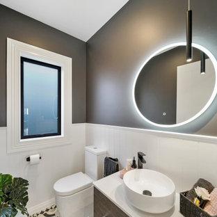 Mittelgroße Gästetoilette mit verzierten Schränken, dunklen Holzschränken, Wandtoilette, weißen Fliesen, grauer Wandfarbe, Mosaik-Bodenfliesen, Aufsatzwaschbecken, Quarzit-Waschtisch, schwarzem Boden, weißer Waschtischplatte, schwebendem Waschtisch, gewölbter Decke und Holzdielenwänden in Auckland