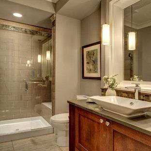 Modelo de aseo clásico con lavabo sobreencimera, armarios estilo shaker, puertas de armario de madera en tonos medios, baldosas y/o azulejos grises, paredes grises y encimeras grises