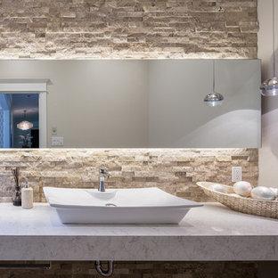 На фото: маленький туалет в современном стиле с бежевой плиткой, бежевыми стенами, настольной раковиной, столешницей из искусственного кварца, унитазом-моноблоком, плиткой из травертина, полом из травертина и бежевым полом с