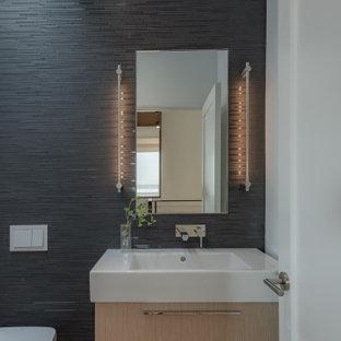 Источник вдохновения для домашнего уюта: туалет среднего размера в современном стиле с плоскими фасадами, светлыми деревянными фасадами, инсталляцией, черной плиткой, черными стенами, монолитной раковиной, столешницей из искусственного камня, бежевым полом, белой столешницей, светлым паркетным полом и плиткой мозаикой