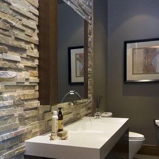 Свежая идея для дизайна: туалет в современном стиле с каменной плиткой и монолитной раковиной - отличное фото интерьера