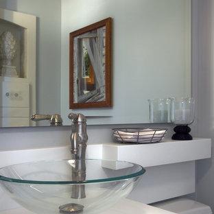 Idée de décoration pour un très grand WC et toilettes design avec une vasque, des portes de placard blanches, un plan de toilette en surface solide, un WC à poser, un mur blanc et un sol en bois brun.