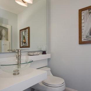 Exemple d'un très grand WC et toilettes tendance avec une vasque, un plan de toilette en surface solide, un WC à poser, un mur blanc, un sol en bois brun et un plan de toilette blanc.