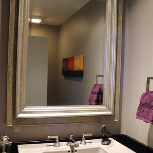 Cette photo montre un WC et toilettes chic de taille moyenne avec une vasque, un mur gris, un placard à porte shaker, des portes de placard en bois brun, un sol en bois brun, un sol beige et un plafond voûté.