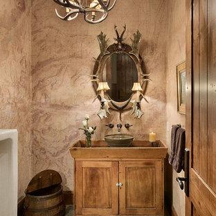 Cette image montre un grand WC et toilettes chalet avec un placard en trompe-l'oeil, des portes de placard en bois clair, un urinoir, une vasque, un plan de toilette en bois, un mur multicolore, un sol en ardoise et un sol multicolore.