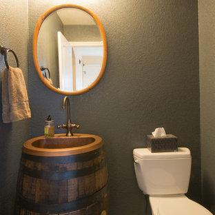 Неиссякаемый источник вдохновения для домашнего уюта: маленький туалет в классическом стиле с накладной раковиной, искусственно-состаренными фасадами, столешницей из меди, раздельным унитазом и серыми стенами
