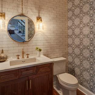 На фото: туалет в стиле фьюжн с фасадами с утопленной филенкой, фасадами цвета дерева среднего тона, раздельным унитазом, белой плиткой, терракотовой плиткой, черными стенами, паркетным полом среднего тона, врезной раковиной, столешницей из кварцита и коричневым полом