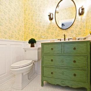 Modelo de aseo tradicional, pequeño, con lavabo bajoencimera, armarios tipo mueble, puertas de armario verdes, sanitario de dos piezas, baldosas y/o azulejos blancos, paredes amarillas y suelo de mármol