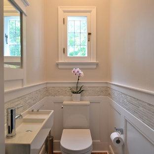 Kleine Klassische Gästetoilette mit Wandwaschbecken, grauen Fliesen, Stäbchenfliesen, Wandtoilette mit Spülkasten, beiger Wandfarbe und braunem Holzboden in Ottawa