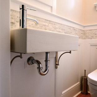 Idée de décoration pour un petit WC et toilettes tradition avec un carrelage gris, un carrelage de pierre, un mur blanc, un sol en bois brun et un lavabo suspendu.