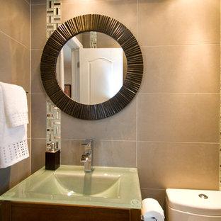 Cette photo montre un petit WC et toilettes tendance avec un placard à porte plane, des portes de placard en bois sombre, un WC séparé, un carrelage beige, des carreaux de porcelaine, un mur beige, un sol en carrelage de porcelaine, un lavabo intégré et un plan de toilette en verre.