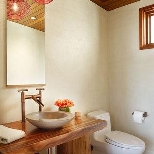 ロサンゼルスの中サイズのトロピカルスタイルのおしゃれなトイレ・洗面所 (ベッセル式洗面器、オープンシェルフ、濃色木目調キャビネット、ベージュの壁、磁器タイルの床、木製洗面台、茶色い床、ブラウンの洗面カウンター) の写真