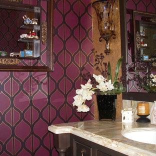 Cette photo montre des petits WC et toilettes éclectiques avec un placard avec porte à panneau encastré, des portes de placard en bois sombre, un mur violet, un lavabo encastré et un plan de toilette en granite.