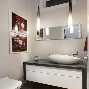 На фото: огромный туалет в современном стиле с плоскими фасадами, белыми фасадами, инсталляцией, бежевой плиткой, серыми стенами, светлым паркетным полом и настольной раковиной с