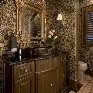 На фото: класса люкс большие туалеты в классическом стиле с настольной раковиной, фасадами с выступающей филенкой, коричневыми фасадами, столешницей из гранита, унитазом-моноблоком, бежевой плиткой и полом из травертина