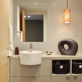 На фото: маленький туалет в стиле модернизм с серыми фасадами, белой плиткой, стеклянной плиткой, белыми стенами, монолитной раковиной, столешницей из искусственного кварца, плоскими фасадами и серым полом с