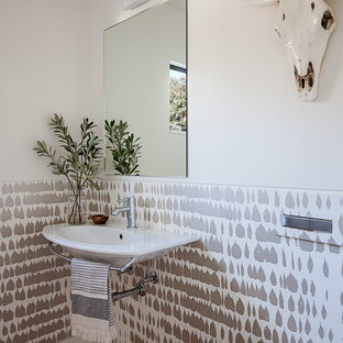 Photo of a small contemporary cloakroom in San Francisco with a wall mounted toilet, white walls, light hardwood flooring and a wall-mounted sink.