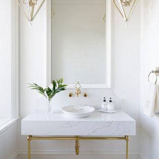 Cette photo montre un WC et toilettes chic de taille moyenne avec un WC à poser, un carrelage blanc, un mur blanc, une vasque, un sol jaune et un plan de toilette blanc.