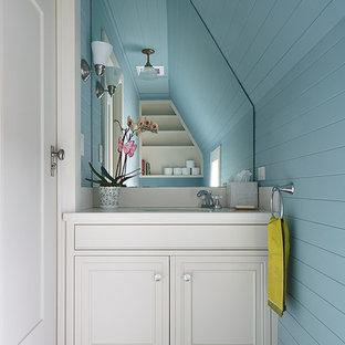 Diseño de aseo clásico, pequeño, con lavabo bajoencimera, armarios con rebordes decorativos, puertas de armario blancas, encimera de acrílico, paredes azules y suelo de madera pintada