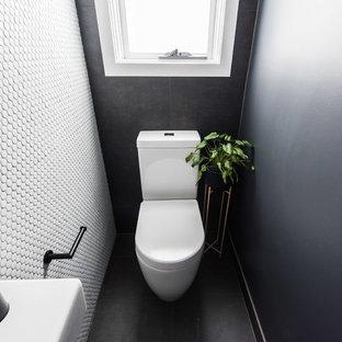 Ispirazione per un bagno di servizio design con WC monopezzo, pistrelle in bianco e nero, piastrelle a mosaico, pavimento in gres porcellanato, lavabo sospeso e pavimento nero