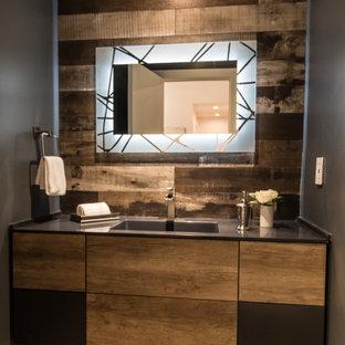 ロサンゼルスの中くらいのコンテンポラリースタイルのおしゃれなトイレ・洗面所 (フラットパネル扉のキャビネット、中間色木目調キャビネット、一体型トイレ、黒い壁、淡色無垢フローリング、一体型シンク、クオーツストーンの洗面台、ベージュの床、黒い洗面カウンター、フローティング洗面台、板張り壁) の写真