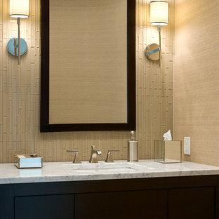 Идея дизайна: маленький туалет в стиле современная классика с врезной раковиной, плоскими фасадами, темными деревянными фасадами, мраморной столешницей, стеклянной плиткой, бежевыми стенами и белой столешницей