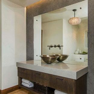 Пример оригинального дизайна: туалет среднего размера в современном стиле с настольной раковиной, плоскими фасадами, столешницей из искусственного кварца, коричневой плиткой, металлической плиткой, серыми стенами, полом из известняка и темными деревянными фасадами