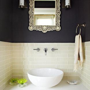 Idée de décoration pour un petit WC et toilettes design avec une vasque, un placard à porte plane, des portes de placard en bois brun, un plan de toilette en quartz modifié, un mur noir, un carrelage beige et un plan de toilette blanc.