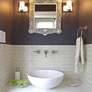 На фото: маленький туалет в современном стиле с настольной раковиной, серой плиткой, стеклянной плиткой и столешницей из искусственного кварца с