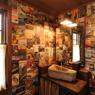 Bild på ett mellanstort rustikt brun brunt toalett, med ett fristående handfat, släta luckor, träbänkskiva, mörkt trägolv och skåp i mörkt trä