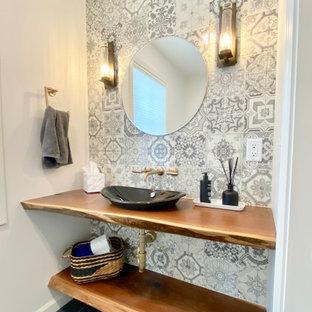 Inspiration pour un WC et toilettes rustique de taille moyenne avec un carrelage gris, des carreaux de céramique, un mur blanc, un sol en ardoise, une vasque, un plan de toilette en bois, un sol noir, un plan de toilette marron et meuble-lavabo suspendu.