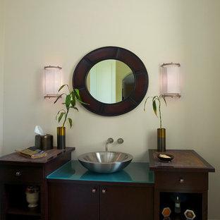 Ispirazione per un grande bagno di servizio chic con consolle stile comò, ante in legno bruno, piastrelle beige, piastrelle in pietra, pareti beige, pavimento in pietra calcarea, lavabo a bacinella e top in vetro