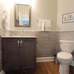 Immagine di un piccolo bagno di servizio tradizionale con ante lisce, ante grigie, WC a due pezzi, pareti beige, pavimento in legno massello medio, lavabo da incasso, top in superficie solida, pavimento marrone e top bianco