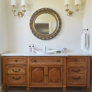 Inspiration for a large cottage gray floor powder room remodel in Chicago with furniture-like cabinets, medium tone wood cabinets, white walls, a vessel sink, white countertops and quartzite countertops