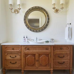 Große Landhaus Gästetoilette mit verzierten Schränken, hellbraunen Holzschränken, weißer Wandfarbe, Aufsatzwaschbecken, grauem Boden, weißer Waschtischplatte und Quarzit-Waschtisch in Chicago