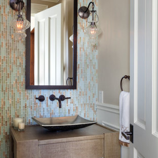 This is an example of a small traditional cloakroom in Boston with multi-coloured tiles, glass tiles, beige walls and a vessel sink.