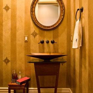 Стильный дизайн: туалет среднего размера в классическом стиле с настольной раковиной, фасадами островного типа, темными деревянными фасадами, стеклянной столешницей, унитазом-моноблоком, желтой плиткой, желтыми стенами, темным паркетным полом, коричневым полом и коричневой столешницей - последний тренд