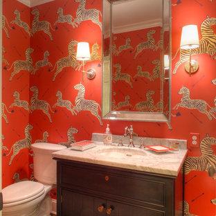 Modelo de aseo ecléctico, pequeño, con lavabo bajoencimera, puertas de armario de madera en tonos medios, encimera de mármol, sanitario de dos piezas, armarios con rebordes decorativos, suelo de madera en tonos medios, paredes rojas y encimeras blancas