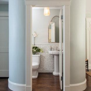 Modelo de aseo tradicional, pequeño, con lavabo con pedestal, sanitario de dos piezas, baldosas y/o azulejos blancos, baldosas y/o azulejos en mosaico, paredes blancas y suelo de madera oscura