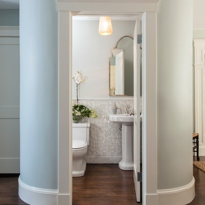 Small elegant white tile and mosaic tile dark wood floor powder room photo in Boston with a pedestal sink, a two-piece toilet and white walls